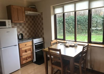 Kitchen area of apartment 4 with dining chairs and table, cooker and fridge freezer