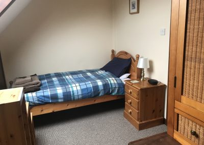 Bedroom of apartment 4 showing single bed and bedside table