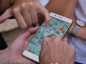 Three friends looking at a map on a phone.  One person is pointing to a location.